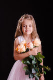 Sad five year old girl with a bouquet of flowers Stock Photos