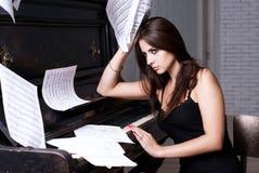 SAD flicka nära piano Arkivbild