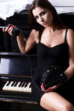 SAD flicka nära piano med den retro telefonen Royaltyfri Bild