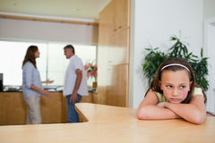 SAD flicka som lyssnar till stridighetföräldrar royaltyfri foto