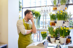 Sad florist man or seller at flower shop counter Stock Image