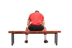 Sad football player sitting on a wooden bench Royalty Free Stock Photography