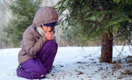 Sad freezing girl trying to stay warm in winter forest. Freezing girl sitting near a fir-tree trying to warm up her cold hands Royalty Free Stock Photography