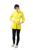 Sad freezing woman in yellow raincoat with hands in pockets Royalty Free Stock Photography