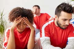 Sad friends or football fans at home Stock Images
