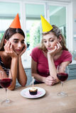 Sad friends with hand on chin while sitting at table during birthday party Royalty Free Stock Photo
