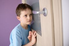 Sad, frightened child listening to a parent talking through the door. With a glass pressed to his ear royalty free stock photography