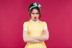 Sad frowning pinup girl standing with arms crossed. Sad frowning pinup girl in yellow dress standing with arms crossed over pink background stock photos