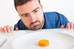Sad and frustrated man on diet having only vegetables for meal Royalty Free Stock Photos