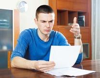 Sad frustrated man looking at piece of paper Stock Photos