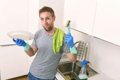 Sad and frustrated man washing the dishes and making home kitchen sink clean feeling tired. Young sad and frustrated man washing the dishes and making home Royalty Free Stock Image