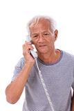 Sad, frustrated, negative senior old man using telephone Royalty Free Stock Photos