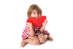 Sad funny Girl child in red plaid dress with red paper  heart,. Valentine`s Day concept, isolated on  white background Stock Image
