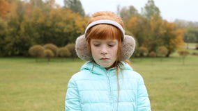 Sad ginger girl in the earmuffs stock footage