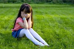 Sad Girl. Young brunette girl sitting on a grass lawn, her hands flat on each side of her face. She has a sad expression, and is looking downward Stock Photo