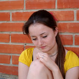 Sad girl. Sitting by brick wall Royalty Free Stock Photo