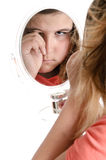 Sad Girl. A sad girl is crying while looking at the viewer in a mirror, isolated against a white background Royalty Free Stock Photo
