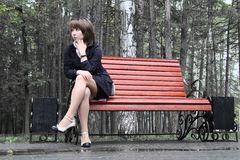 Sad girl. Sitting on a wet bench in a park in rainy day Royalty Free Stock Image