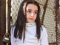 Sad girl. In front of a wire fence royalty free stock photography