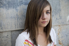 Sad Girl. Teenage girl with sombre expression against grunge wall Royalty Free Stock Photos