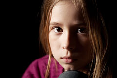 Sad girl. Sad child on black background. Portrait depression girl Stock Images