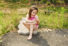 Sad Girl. Little girl sitting on a stone looking really sad Stock Images