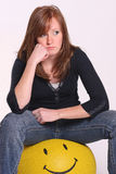 Sad girl. A sad young girl sitting on a smiley face ball royalty free stock image