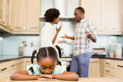 Sad girl against parents arguing. In the kitchen Stock Photo