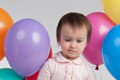 Sad girl with balloons. Sad baby girl with balloons Stock Photo