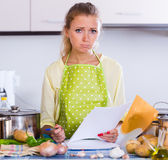 Sad girl with banking statement at home Stock Image