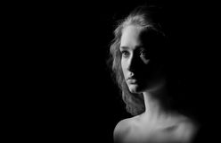 Sad girl with bared shoulders. Looks in camera on black background, monochrome image Stock Photo