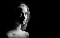 Sad girl with bared shoulders. Looks in camera on black background, monochrome image Royalty Free Stock Image