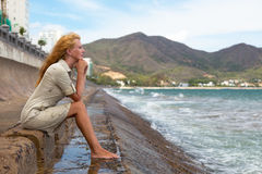 The sad girl. Beautiful red-haired girl sitting on the beach and crying stock photo