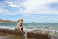The sad girl. Beautiful red-haired girl sitting on the beach and crying royalty free stock photography
