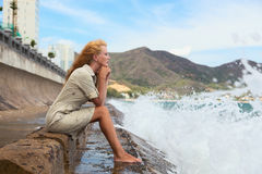 The sad girl. Beautiful red-haired girl sitting on the beach and crying royalty free stock images