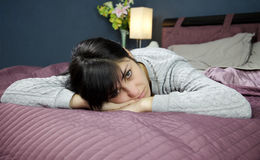 Sad girl in bed looking camera unhappy lying Royalty Free Stock Photography