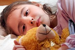 Sad girl in bed with teddy Royalty Free Stock Photos