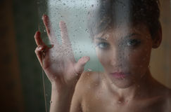 Sad girl. Girl behind the glass with rain drops stock photo