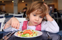 Sad girl behind table in cafe Royalty Free Stock Photos