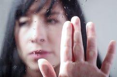 Sad girl behind wet glass Stock Image
