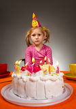 Sad girl with birthday cake. Little sad girl sitting in front of birthday cake Royalty Free Stock Photography