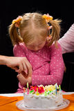 Sad girl with birthday cake. Little sad girl sitting in front of birthday cake Royalty Free Stock Image