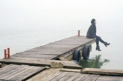 Sad girl in black clothes  sitting on the wooden river dock Stock Photo