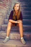 Sad girl with blue eyes sitting at stone brick stairs Royalty Free Stock Images