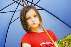 Sad Girl With Blue Umbrella. Young girl with an umbrella, very sad that it is raining Stock Images