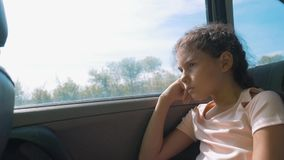 Sad girl bored sitting in the car in the back seat motion travel . little girl bored in the car. concept lifestyle kid. Sad girl bored sitting in the car in the stock video
