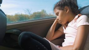 Sad girl bored sitting in the car in the back seat motion travel . little girl bored in the car. concept kid car. Sad girl bored sitting in the car in the back stock video footage