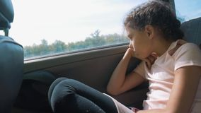 Sad girl bored sitting in the car in the back seat motion travel . little girl bored in the car. concept kid lifestyle. Sad girl bored sitting in the car in the stock footage