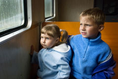 Sad girl and boy. The sad girl and boy looking through a wet window of the train Royalty Free Stock Photo