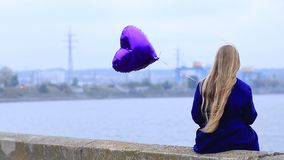 Sad girl with broken heart holding heart balloon stock video